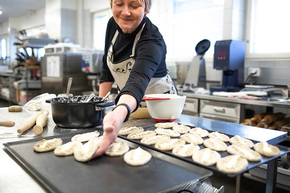 Essuun pukeutunut nainen asettaa keittiössä uunipellille raakaa karjalanpiirakkaa. Pöydällä uunipeltien päällä on jo useita paistamattomia piirakoita.