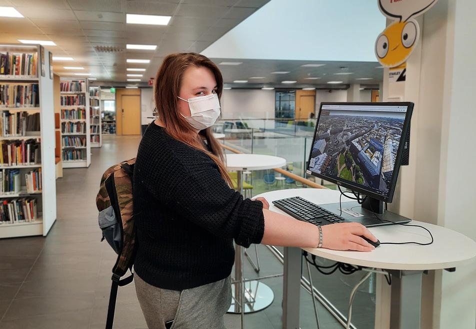 Mia Väntti seisoo kirjastossa tietokoneen äärellä maski kasvoillaan ja katsoo kameraan olkansa yli.