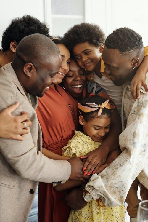 Kuvituskuvassa ryhmä tummaihoisia henkilöitä halaa toisiaan ja hymyilee.
