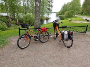 Kaksi polkupyörää pyöräparkkitelineessä järven rannassa