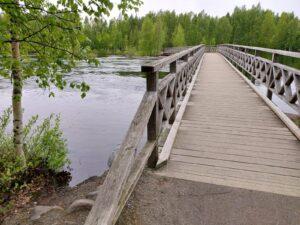 Puinen kävelysilta yli virtaavan joen
