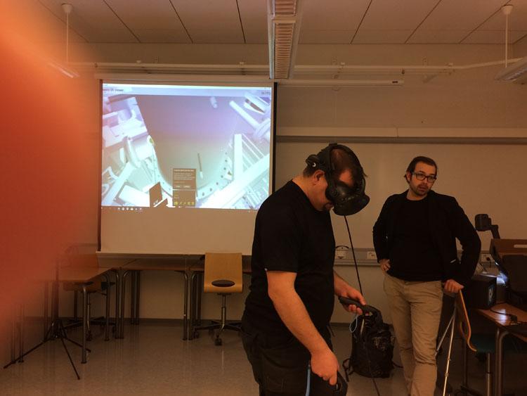 Tutkimusinsinööri Marko Pekkarinen tutkii Energiatutkimuskeskuksen VR-mallia yhdessä Sweco Oy:n Jarkko Heikuran kanssa.