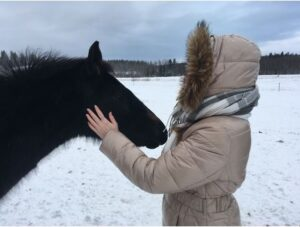 A girl with a horse in a snowy place.