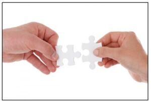 Kaksi kättä, jotka pitelevät kahta toisiinsa sopivaa palapelin palaa.
