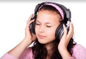 Tyttö kuuntelee kuulokkeilla ja nauttii.