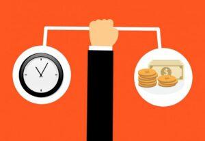 Käsi, joka pitelee tasapainossa kelloa ja rahakasaa.