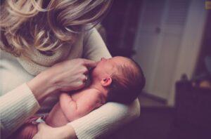 Nainen vauva sylissä.