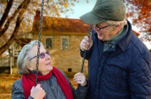 Vanha nainen on kiikussa ja mies seisoo vieressä, he keskustelevat.
