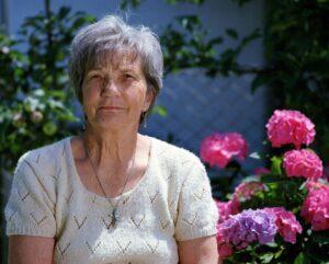 Vanhempi nainen ulkona, kukkia taustalla.