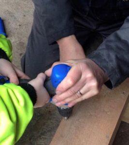 Aikuinen ja lapsi rakentavat linnunpönttöä.