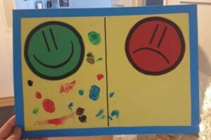 Taulu, jossa hymyilevä ja tyytymätön naama sekä lasten maalaamat jäljet hymynaaman puolella.