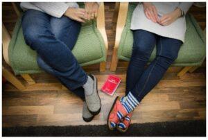 Kaksi ihmistä istuu tuoleissa, vain jalat näkyvät.