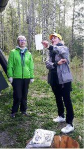 Kaksi naista seisoo luonnossa ja lukee paperista.