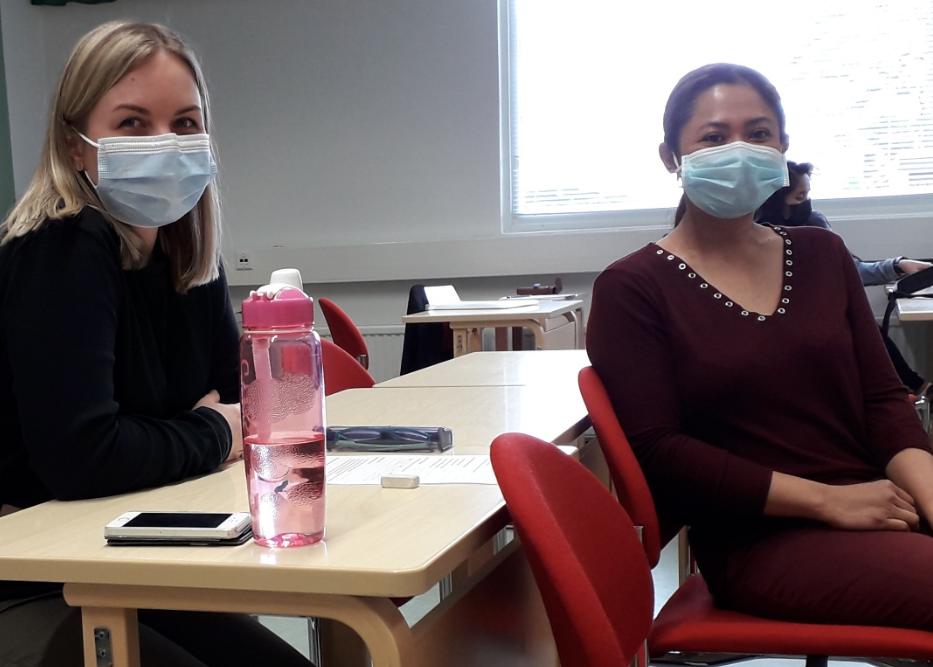 Kaksi opiskelijaa istuu pulpeteissa maskit päässä.