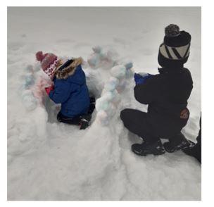 Kaksi lasta leikkii lumessa.