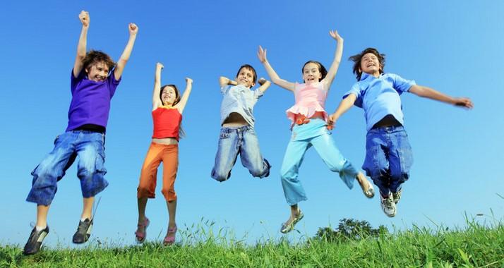 Kuvituskuvassa viisi lasta hyppää ilmaan ja hymyilee katsoen kameraan. Kaikilla on yllään värikkäät vaatteet.