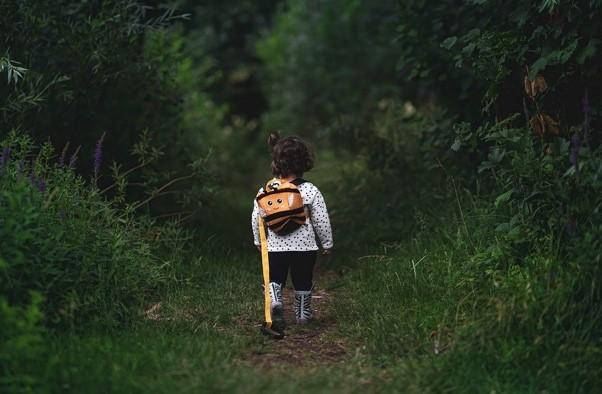 Kuvituskuva. Lapsi seisoo selkä kameran päin reppu selässään ja katsoo metsän siimekseen.