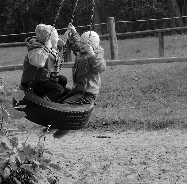 Mustavalkoinen kuva. Kaksi lasta keinuu auton renkaasta tehdyssä keinussa, molemmat hymyilevät.