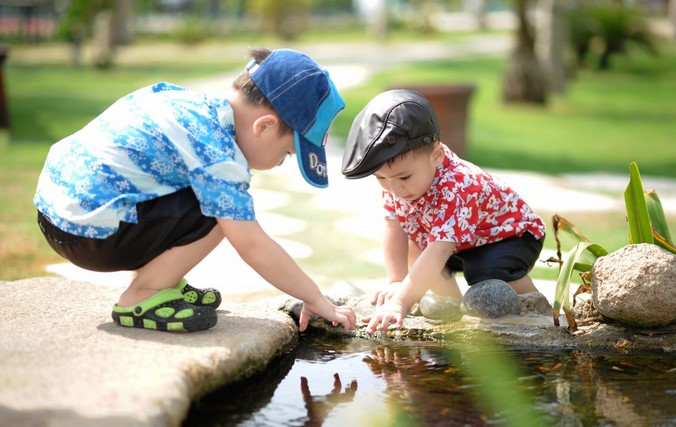 Kaksi lasta kyykistyy lammikon äärelle kesällä, pojilla on värikkäät vaatteet sekä hatut päässä. Molemmat katsovat ihmetellen veteen.