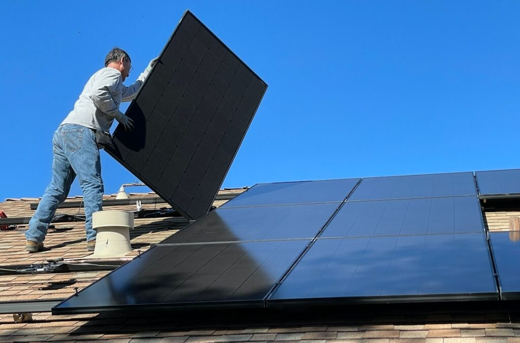 Kuvituskuva, jossa mies asentaa aurinkopaneelia katolle.